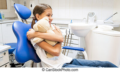 Portrait of happy smiling girl hugging teddy bear in dentist office