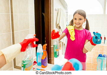 happy smiling girl polishing mirror at bathroom with cloth