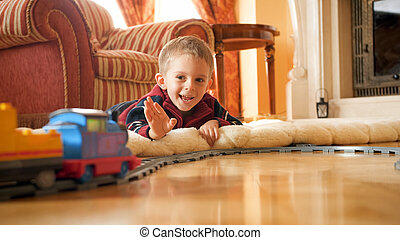 Portrait of happy smiling little boy lying on floor and waving hand to toy train riding on railroad at living room.