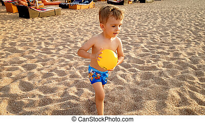 Portrait of happy smiling little boy running and playing with small yellow ball on the sandy sea beach