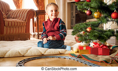 Portrait of happy smiling little boy sitting next to Christmas tree and presents from SAnta Claus at living room
