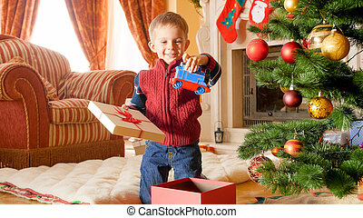 Portrait of happy smiling little boy taking out toy train from Christmas gift box