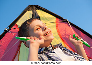 portrait of happy smiling little boy with colorful kite in his hands above head