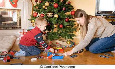 Portrait of happy smiling little boy with mother building railroad and playing with toy train on floor under Beautiful Christmas tree