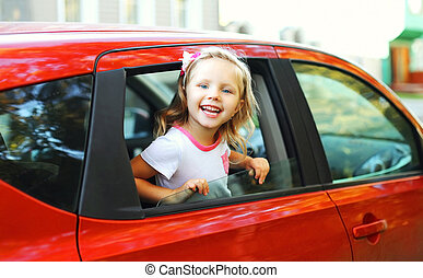 Portrait of happy smiling little child sitting in red car