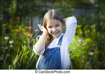 Portrait of happy smiling little girl in sunny garden