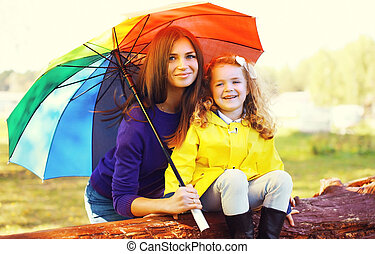 Portrait of happy smiling mother and child with umbrella in autumn day