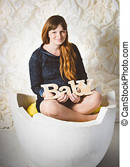 happy smiling pregnant woman sitting in big egg shell