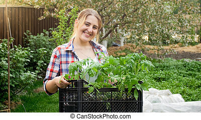 Portrait of happy smiling woman holding box with tomato seedlings