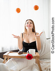 happy smiling woman lying in bed and throwing up oranges -...