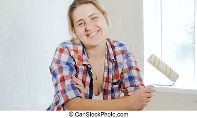 Portrait of happy smiling woman posing with paint roller -...