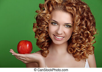 Portrait of happy smiling woman with long glossy hair holding red apple