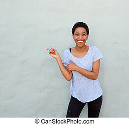 happy smiling young african woman pointing fingers