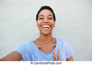 happy smiling young african woman taking selfie