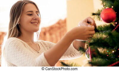Portrait of happy smiling young woman hanging beautiful bauble on branch of Christmas tree at morning