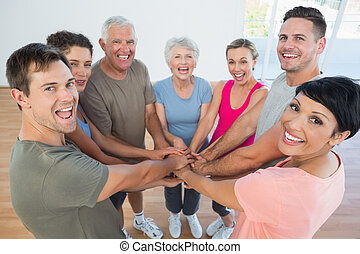 Portrait of happy sporty people holding hands together in...