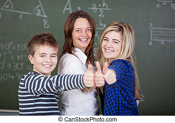 Portrait of happy teacher and students showing thumbsup gesture against blackboard in classroom