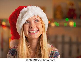 Portrait of happy teenage girl in santa hat looking on copy space