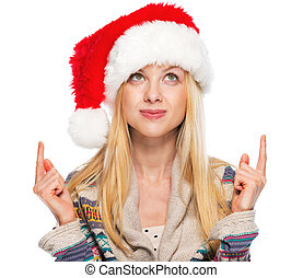 Portrait of happy teenage girl in santa hat pointing on copy space