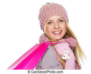 Portrait of happy teenager girl in winter hat and scarf with shopping bag