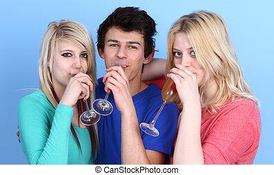 Portrait Of Happy Three Friends Drinking Champagne