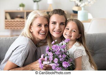 Portrait of happy three generations women family celebrating bir