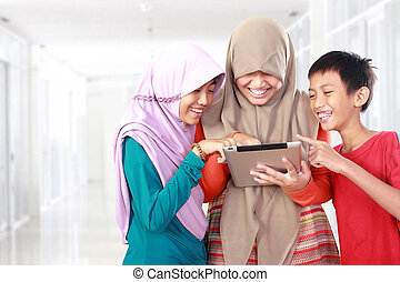 three kids playing tablet computer