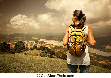 Portrait of happy traveler girl with backpack standing on top of the mountain and enjoying valley view.