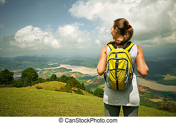 Portrait of happy traveler woman with backpack standing on top of the mountain and enjoying valley view.
