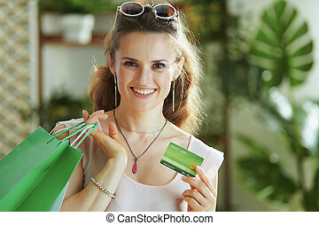 Portrait of happy trendy woman shopper in blouse with bags
