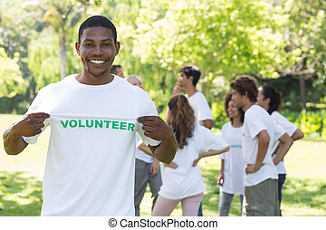 Portrait of happy volunteer holding tshirt with friends...