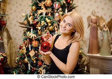 portrait of happy woman decorating Christmas tree