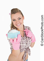Portrait of happy woman holding soap suds over sponge