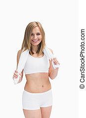 Portrait of happy woman in sportswear holding towel around...