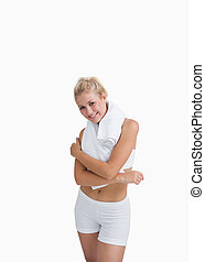 Portrait of happy woman in sportswear holding towel around neck