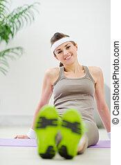 Portrait of happy woman in sportswear sitting on floor