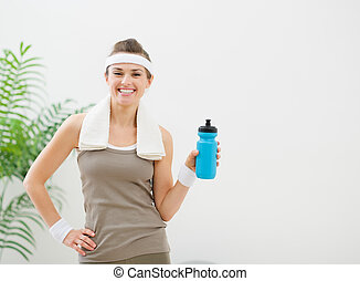 Portrait of happy woman in sportswear with towel and bottle of water