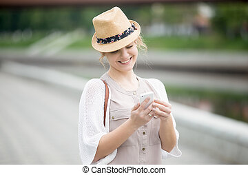 Portrait of happy woman looking at smartphone screen while walking