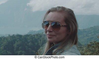 Portrait of happy woman over mountain landscape background
