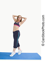 Portrait of happy woman posing on exercise mat