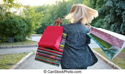 Portrait of happy woman shopaholic spinning outdoors with shopping bags smiling having fun in city park. Consumerism, happiness and lifestyle concept.