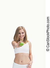 Portrait of happy woman showing a green apple