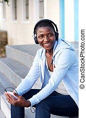 happy woman sitting on steps outside listening to music