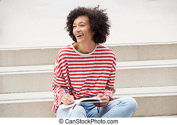 happy woman sitting on steps with book and pen