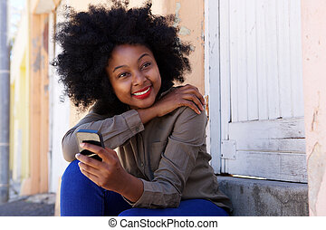 happy woman sitting on steps with mobile phone