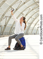 happy woman sitting on suitcase taking selfie