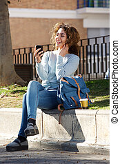 happy woman sitting outside in park looking at cellphone