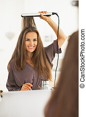 Portrait of happy woman straightening hair with straightener