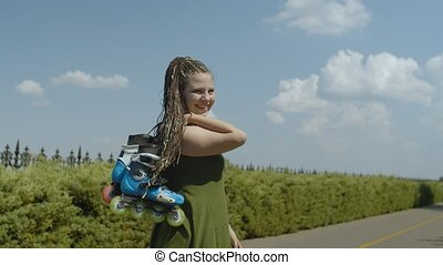 Portrait of happy woman walking with roller blades - Rear...