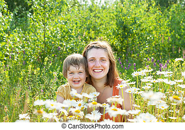 happy woman with baby in camomile plant